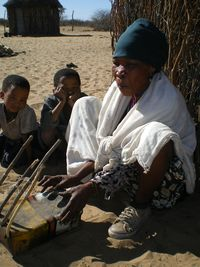 Oba plays the zhoma (pluriarc) while children look on.