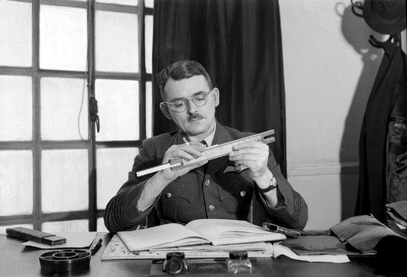Frank Whittle adjusts a slide rule while seated at his desk at the Ministry of Aircraft Production
